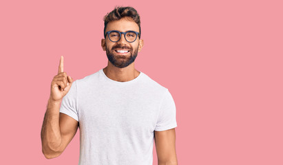 Young hispanic man wearing casual clothes and glasses showing and pointing up with finger number...
