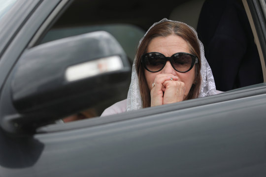 A woman prays inside a car during a drive-in mass celebrated in a parking lot, amidst an outbreak of the coronavirus disease (COVID-19), in Chia