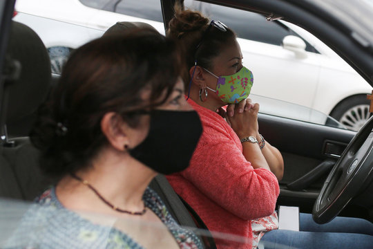 Women wearing face masks pray inside a car during a drive-in mass celebrated in a parking lot, amidst an outbreak of the coronavirus disease (COVID-19), in Chia
