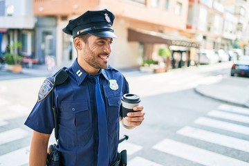 Young hispanic policeman wearing police uniform smiling happy. Drinking cup of take away coffee...