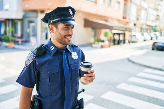 Young hispanic policeman wearing police uniform smiling happy. Drinking cup of take away coffee standing at town street.