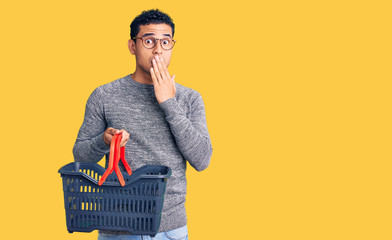 Hispanic handsome young man holding supermarket shopping basket covering mouth with hand, shocked and afraid for mistake. surprised expression