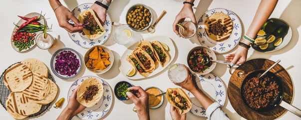 Friends having Mexican Taco dinner. Flat-lay of beef tacos, tomato salsa, tortillas, beer, snacks and peoples hands over white table, top view. Mexican cuisine, gathering, feast, comfort food concept