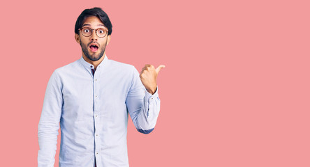 Handsome hispanic man wearing business shirt and glasses surprised pointing with hand finger to the side, open mouth amazed expression.