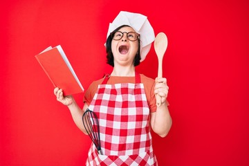 Brunette woman with down syndrome wearing professional baker apron reading cooking recipe book angry and mad screaming frustrated and furious, shouting with anger looking up.