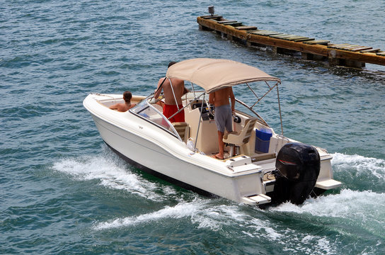 White runabout motorboat with a canvas Bimini top