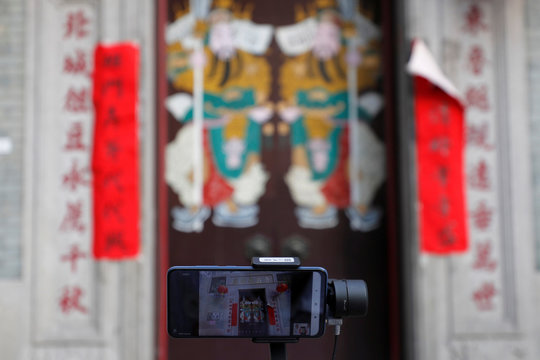 A smart phone films a door of Lo Pan Temple, during a virtual tour, following the coronavirus disease (COVID-19) outbreak in Hong Kong