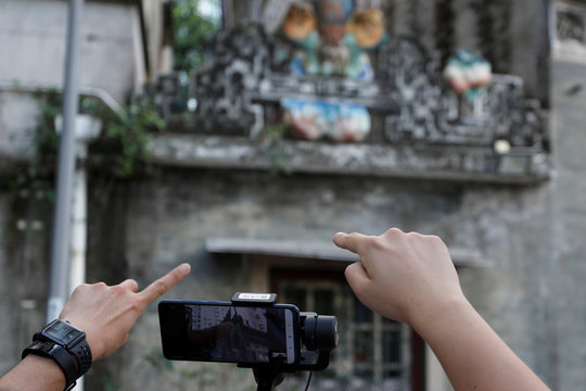 Paul Chan, tour guide and CEO of Walk in Hong Kong, and Charles Lai,  architect, introduce Lo Pan Temple during a live streamed virtual tour, following the coronavirus disease (COVID-19) outbreak in Hong Kong