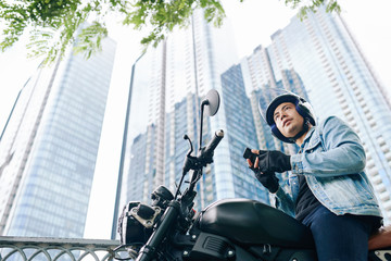 Handsome serious Vietnamese young man in helmet sitting on motorcycle with smartphone in hands, skyscrapers in background