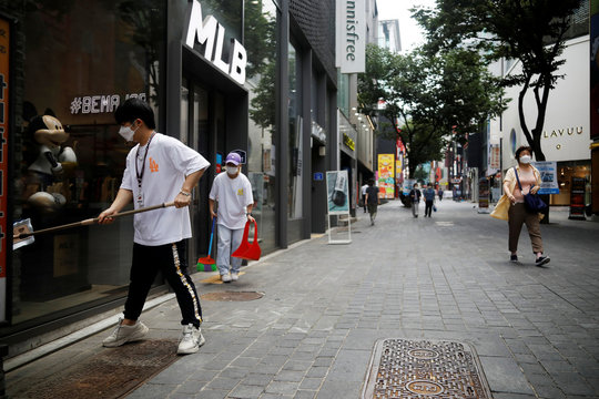 A shop assistant cleans a window as they wait for a customer at Myeongdong shopping district which is nearly empty amid the coronavirus disease (COVID-19) pandemic in Seoul