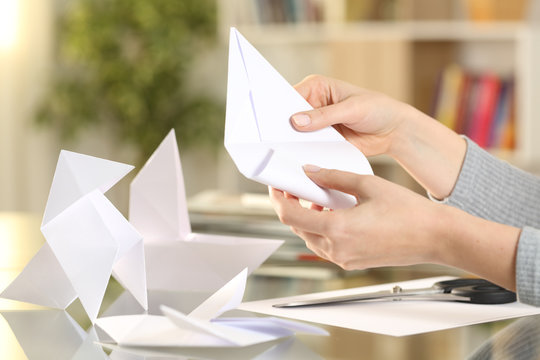 Woman hands doing origami figures at home