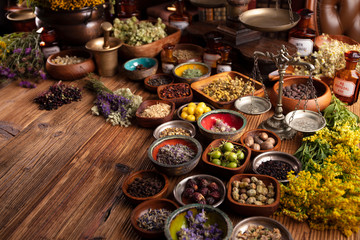 Photo sur Plexiglas Magasin alimentation Natural medicine background. Assorted dry herbs in bowls and brass mortar on rustic wooden table.