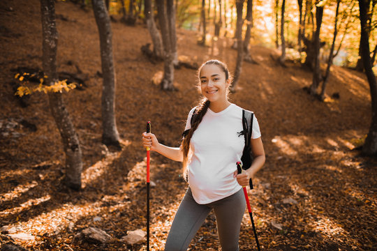 Portrait of young happy pregnant woman nordic walking in autumn forest with backpack and trekking sticks. Healthy, wellness and active lifestyle in maternity time.