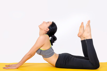 The woman post yoga on the mat in the white backgrounds.
