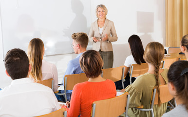 Elegant female teacher lecturing to students in auditorium..