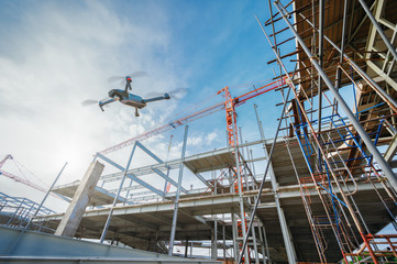 Drone over construction site. video surveillance or industrial inspection. Wall mural