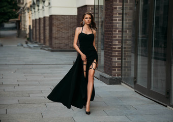Young woman in classic evening black dress. Fashion photo. Luxury girl with long bare leg. Glamour stylish model. Beautiful retro lady walks on old city street. Elegant makeup long wavy hair sexy face
