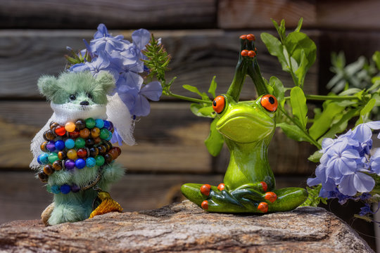 A frog doing yoga and a teddy bear being bound by a bracelet of prayer beads