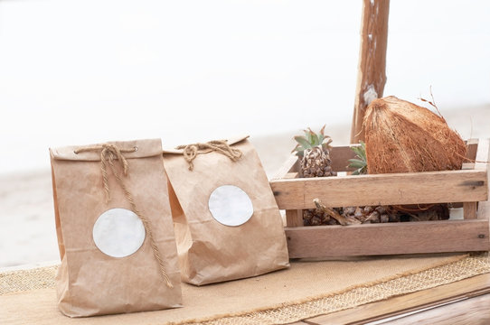Brown paper bags wooden case contain dry coconut and palm on wood table with over light background.