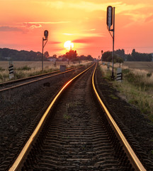 sun is setting over the railroad tracks