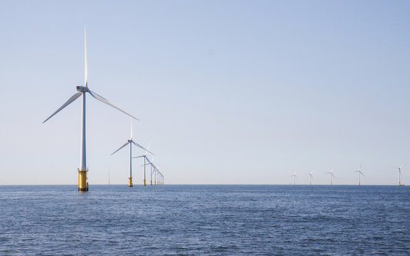 Wind turbines in an offshore wind farm in the North Sea just off the coast of the Netherlands, on a clear day.