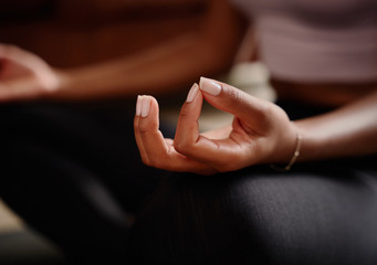 Closeup of young female hand mudra while sitting in lotus position and meditating