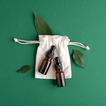 Eco-friendly bio cosmetics set on green background. Zero waste beauty products - serum amber glass dropper bottles and cotton bag with green plant leaves. Flat lay, top view.