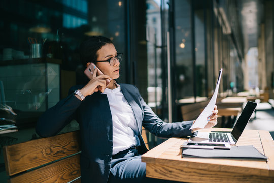 Busy female calling on mobile phone during remote work