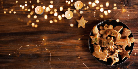 Tasty baked christmas cookies Tasty golden brown baked christmas cookies on a plate with a chain of lights on rustic wood. Background with festive bokeh and space for text. Top view.