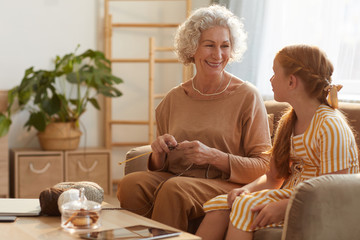 Warm toned portrait of smiling senior woman knitting with cute girl watching her in cozy home lit by sunlight, copy space