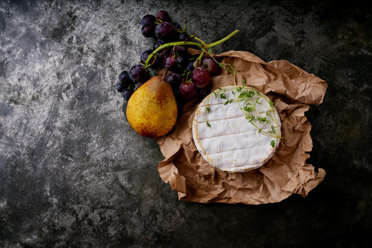 French cheese Camembert with fruits and herbs on the paper over dark rustic background. Top view. Copy space