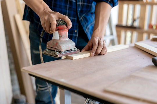 Craftsman hands polishing wooden table with machine.