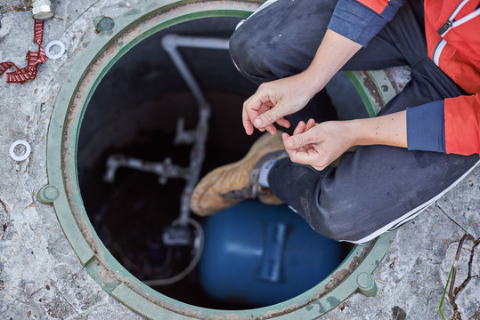 Young plumber or technician sitting on opened hatch of system of water filtration on the street in the home yard