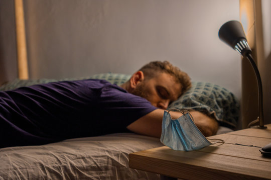 short blond hair young man lying on his stomach sleeping with a mask on top of the bed table focused on the foreground