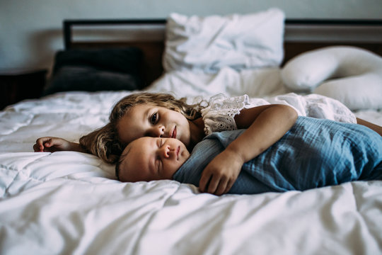 Portrait of girl snuggling her newborn brother on bed at home