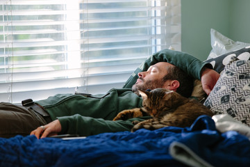 Man takes a cat nap with his tabby cat snuggling next to him