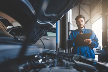Auto mechanic fills in car repair documentation.