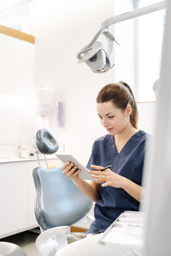 Young nurse wearing a blue jacket smiles in the dental office be
