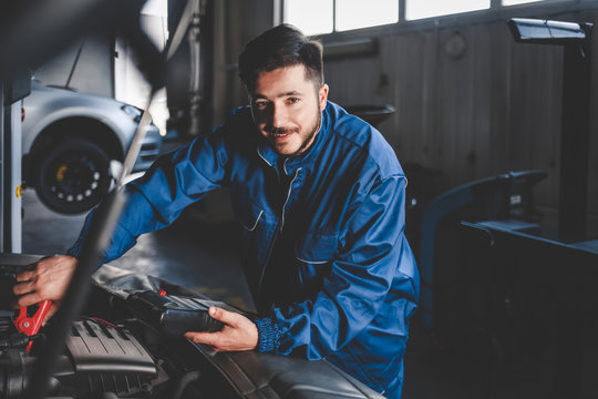 Auto mechanic with a electric device checks the condition