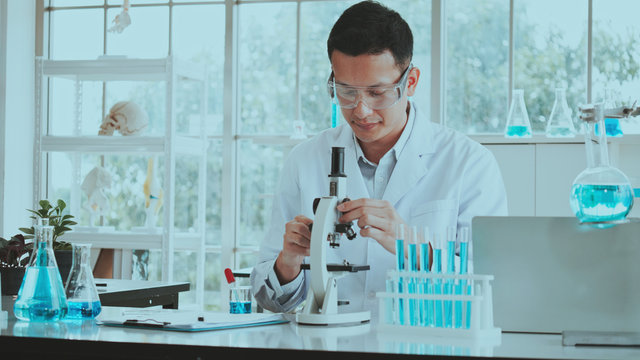 Asian scientist or doctor use microscope to test for the coronavirus (COVID-19). Or cancer to save people life In ab Or hospital. Successful in researching the treatment of patient