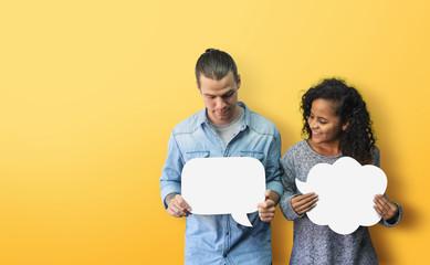 Happy Diversity couple holding white speech bubble on yellow background