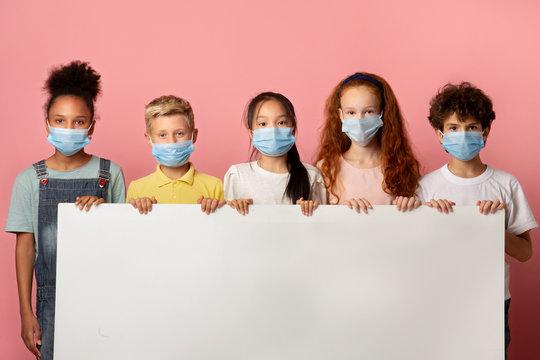 Diverse kids in face masks holding empty poster over pink background, mockup for design