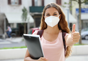 COVID-19 Optimistic student girl with protective mask shows thumb up in city street. College girl back to school after pandemic coronavirus disease 2019.