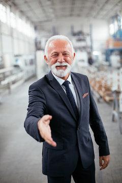 Portrait of handsome businessman. Man handshake in factory...