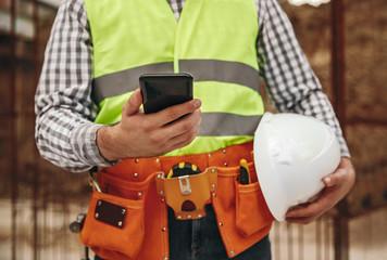Crop contractor using smartphone during break