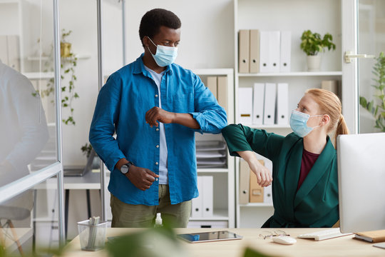 Portrait of young African-American man wearing mask bumping elbows with female colleague as contactless greeting in post pandemic office, copy space
