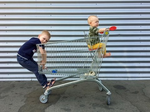 boys in a grocery cart on a metal background