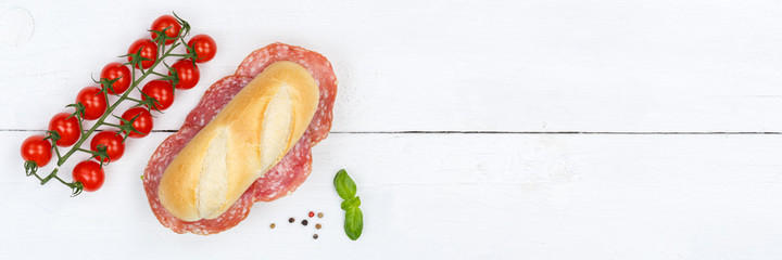 Sub sandwich with salami copyspace copy space banner from above on wooden board