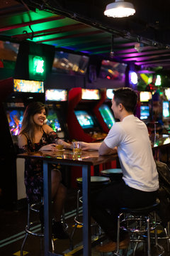 a young couple in a bar arcade