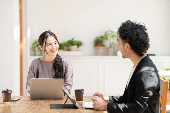 会社でパソコンを使いながらミーティングをするソーシャルディスタンスの若い男女のズーム